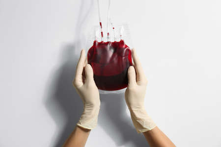 Woman holding blood for transfusion on light background, closeup. Donation concept