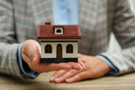 Real estate agent holding house model at wooden table, closeup