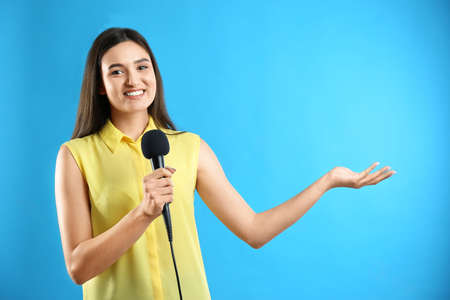 Young female journalist with microphone on blue background Archivio Fotografico