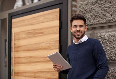 Jonge mannelijke ondernemer met tablet in de buurt van zijn café. Ruimte voor tekst Stockfoto