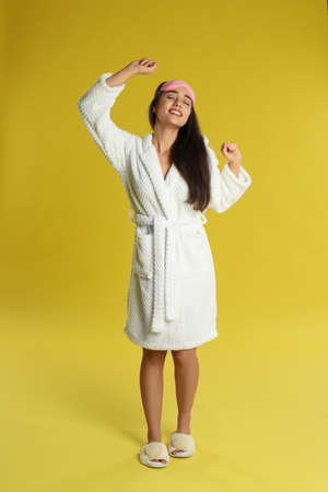 Beautiful young woman in bathrobe and eye sleeping mask stretching on yellow background