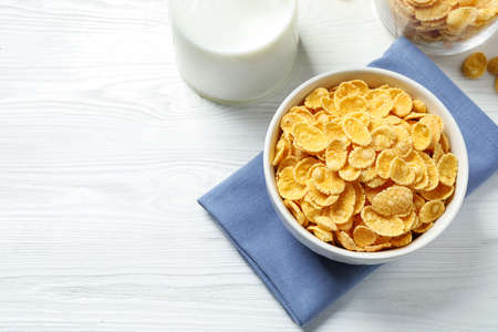 Tasty corn flakes on white wooden table, flat lay. Space for text Foto de archivo