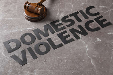 Words DOMESTIC VIOLENCE and gavel on grey marble table Stock Photo