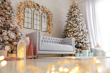 Beautiful interior of living room with decorated Christmas trees, low angle view