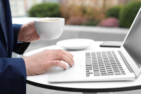 Businessman with laptop and coffee in outdoor cafe, closeup. Corporate blog