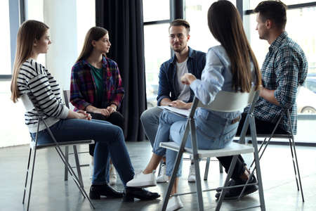 Psychotherapist working with patients in group therapy session indoors Foto de archivo
