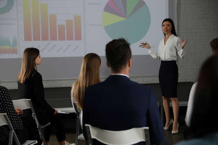 Female business trainer giving lecture in conference room with projection screen Stock fotó