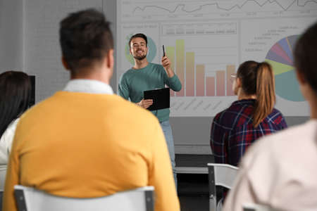 Male business trainer giving lecture in conference room with projection screen Stockfoto