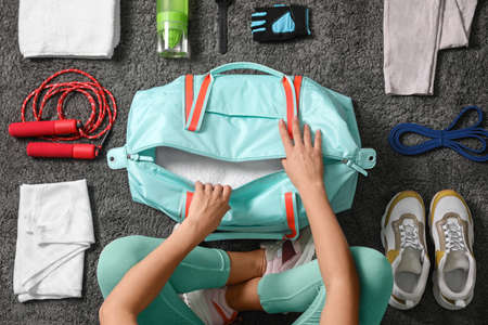 Woman with bag and sports items on grey carpet, top view Stock Photo