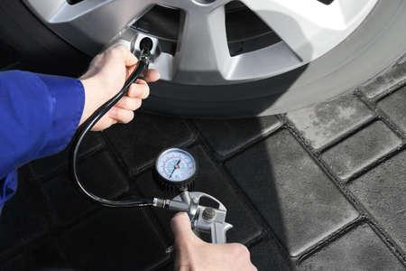 Mechanic checking tire air pressure at car service, closeup