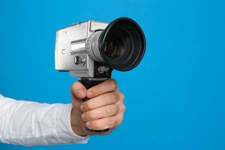 Man with vintage video camera on light blue background, closeup of hand