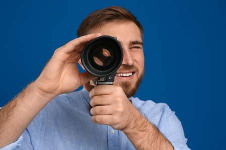 Young man using vintage video camera on blue background, focus on lens