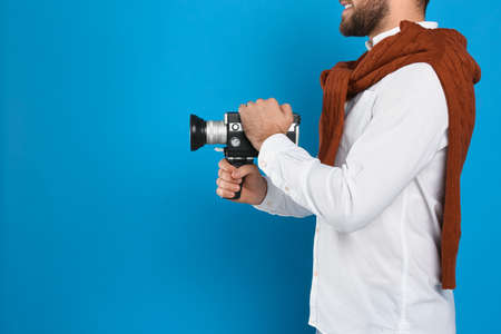 Man with vintage video camera on light blue background, closeup. Space for text