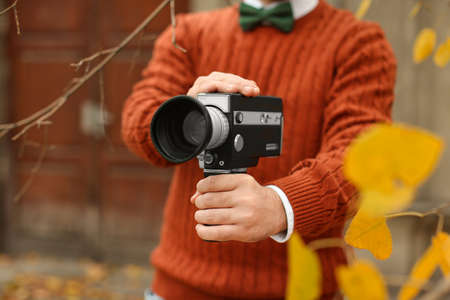 Young man with vintage video camera outdoors, closeup