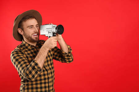 Young man with vintage video camera on red background. Space for text