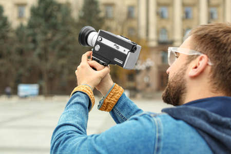 Young man with vintage video camera on city street, closeup