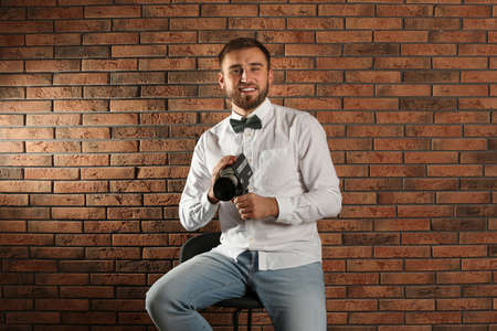 Young man with vintage video camera near brick wall