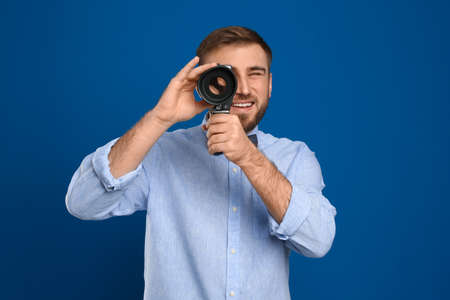 Young man using vintage video camera on blue background