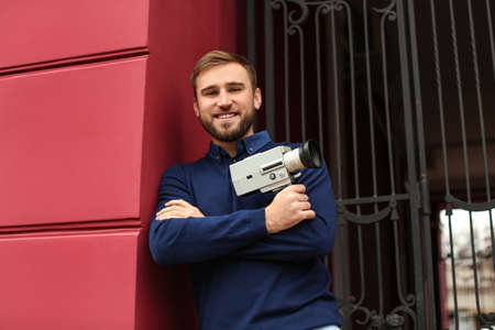 Young man with vintage video camera outdoors