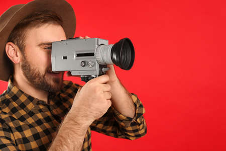 Young man with vintage video camera on red background