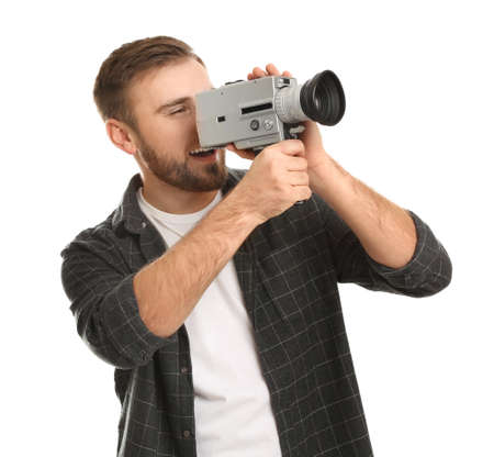 Young man using vintage video camera on white background