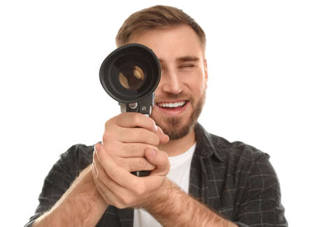 Young man with vintage video camera on white background, focus on lens