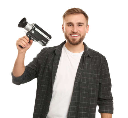Young man with vintage video camera on white background