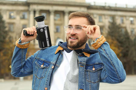 Young man with vintage video camera on city street
