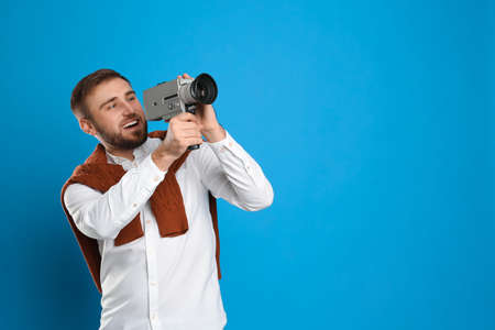 Young man with vintage video camera on light blue background, space for text