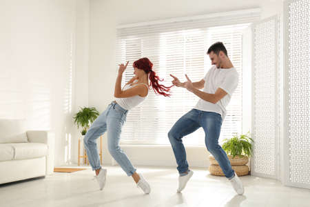 Beautiful young couple dancing in living room