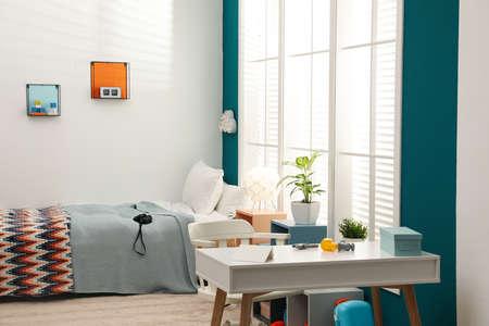 Modern child room interior with comfortable bed near window Foto de archivo