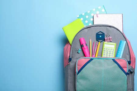 Stilvoller Rucksack mit verschiedenen Schulpapieren auf hellblauem Hintergrund, Draufsicht. Platz für Text