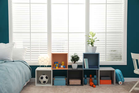 Modern child room interior with big window and comfortable bed