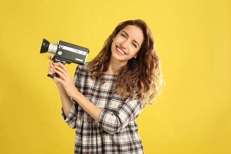 Beautiful young woman with vintage video camera on yellow background Stock Photo