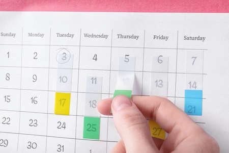 Woman marking date in calendar with sticker, closeup Stock Photo