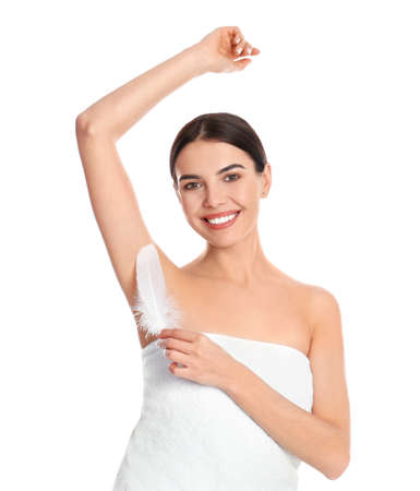 Young woman touching armpit with feather after epilation procedure on white background