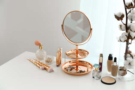 Small mirror and different makeup products on table indoors