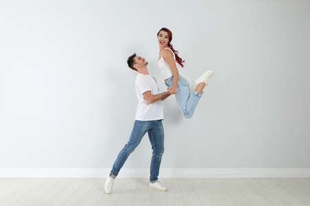 Beautiful young couple dancing near light wall