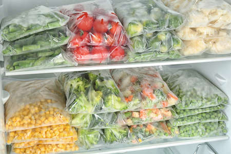 Bolsas de plástico con diferentes verduras congeladas en el frigorífico. Foto de archivo