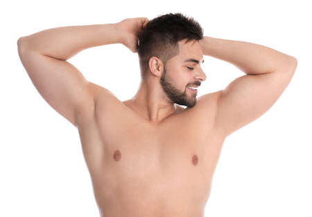 Young man showing hairless armpits after epilation procedure on white background