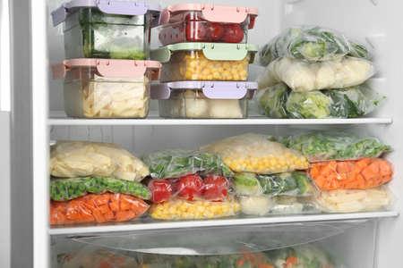 Sacs et récipients en plastique avec différents légumes surgelés au réfrigérateur
