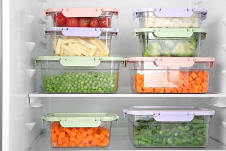Containers with different frozen vegetables in refrigerator