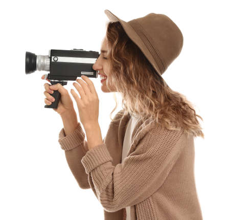 Beautiful young woman using vintage video camera on white background