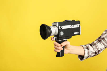 Woman with vintage video camera on yellow background, closeup of hand