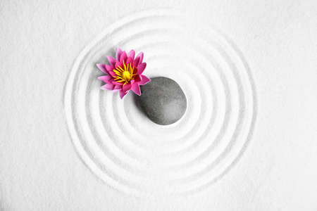 Zen garden. Beautiful lotus flower and stone on white sand, flat lay