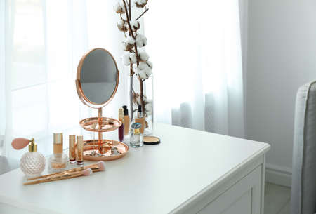 Small mirror and different makeup products on chest of drawers indoors. Space for text Stock fotó