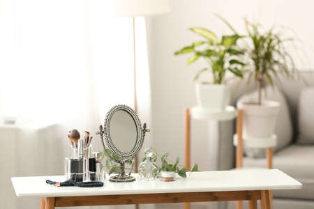 Mirror and makeup products on white table indoors. Space for text