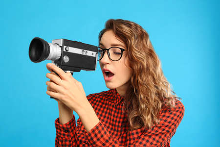 Beautiful young woman with vintage video camera on light blue background