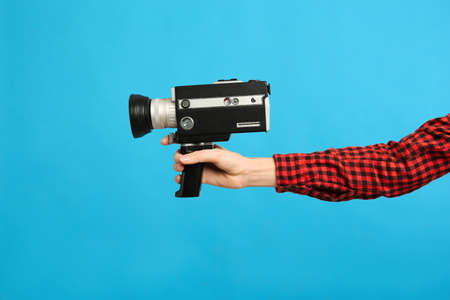 Woman with vintage video camera on light blue background, closeup of hand