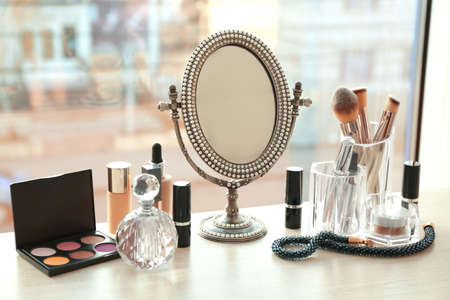 Mirror and makeup products on table near window indoors